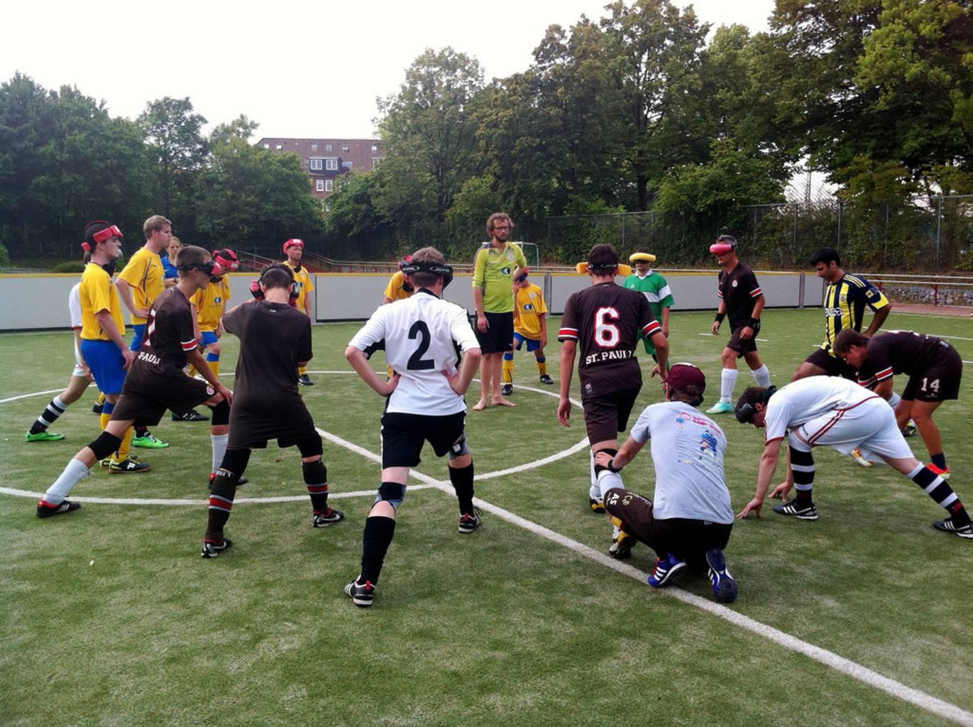 Spieler beider Mannschaften bilden einen großen Kreis auf dem Spielfeld und dehnen sich.