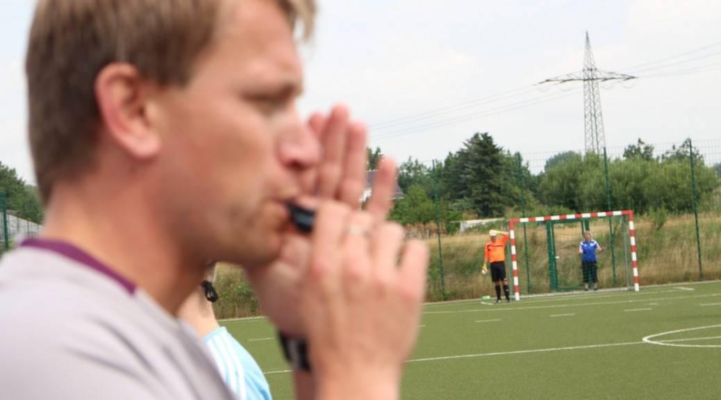 Schiedsrichter pfeift ein Spiel an