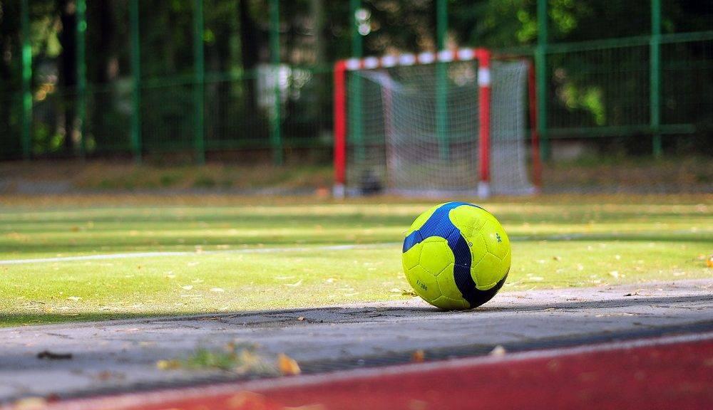 Ball vor einem Fußballplatz mit einem Tor im Hintergrund