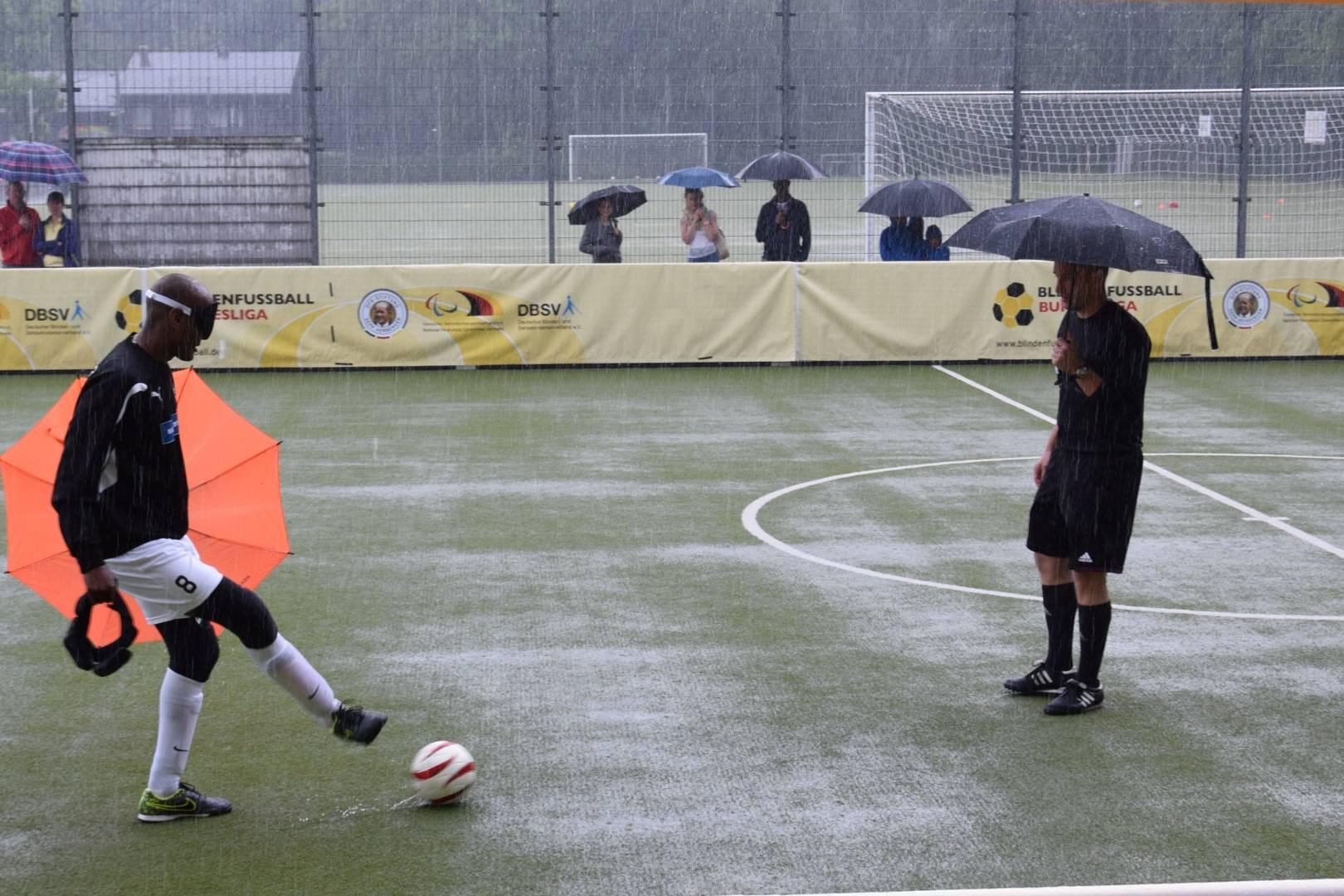 Schiedsrichter Christian Jung und Mulgheta Russom testen die Beschaffenheit des nassen Platzes