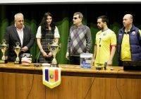 Menschen hiner Tisch an dem ein Rumäischer Wimpel hängt. Darauf zwei Pokale, ein Blindenfußball sowie eine Brille