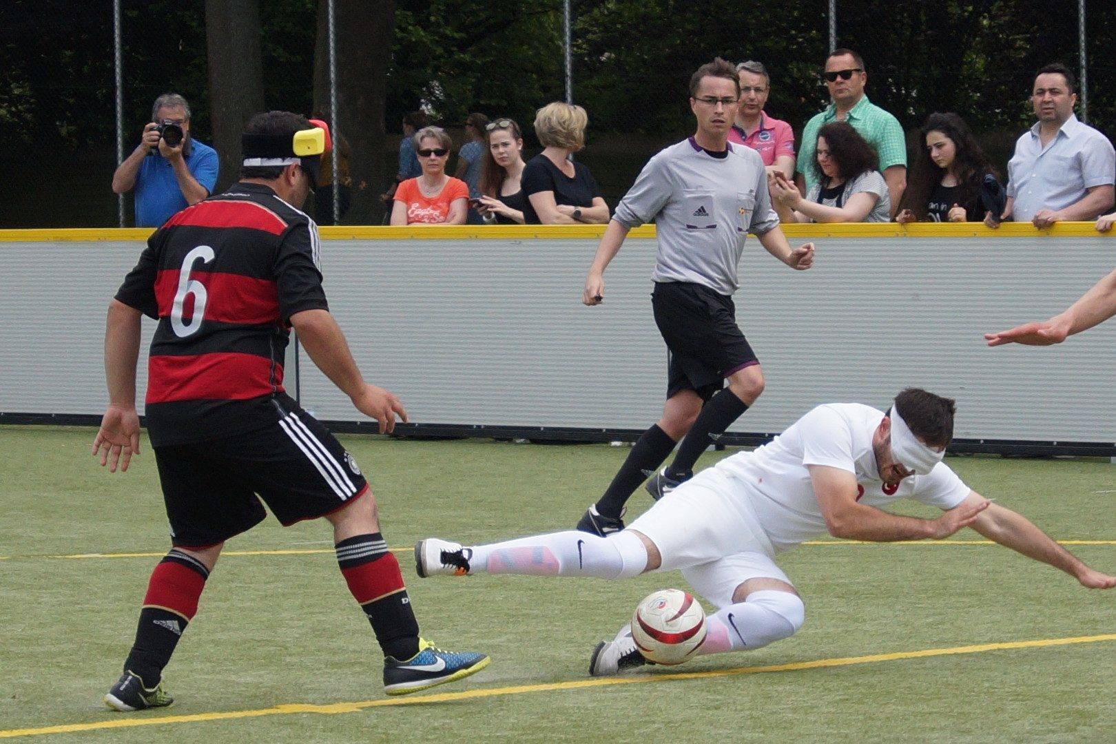 Türkischer Spieler kommt zu Fall, während er versucht den Ball zu schießen.