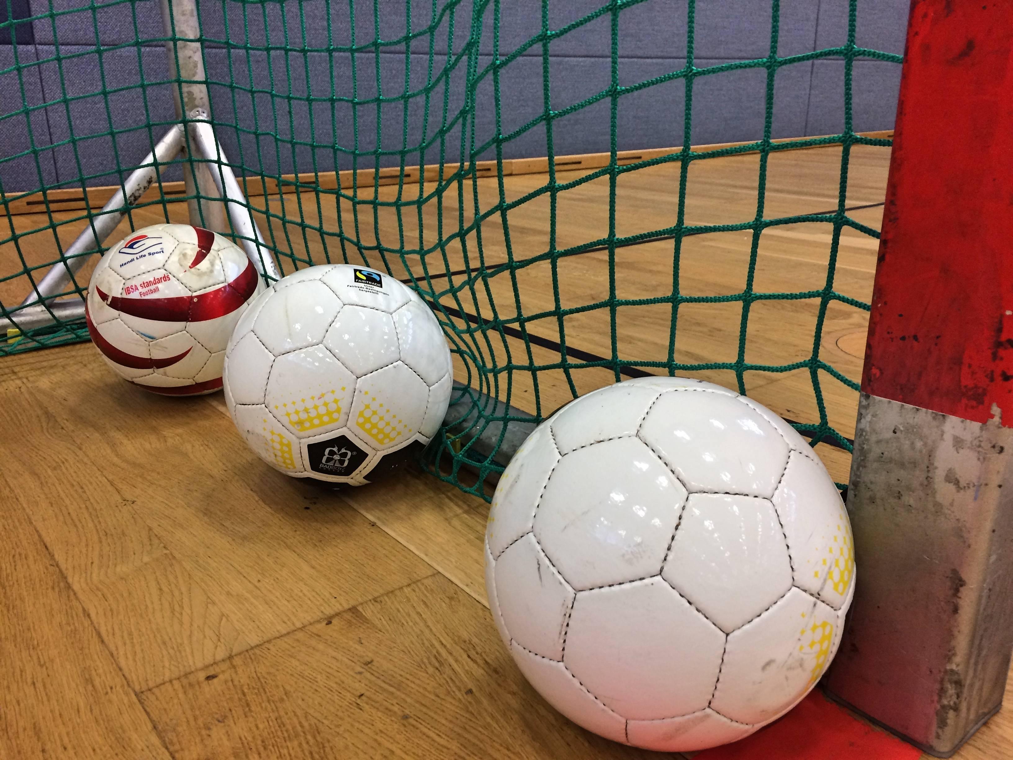 Drei Blindenfußbälle liegen hintereinander in der Ecke eines Handballtores. Foto: Florian Eib