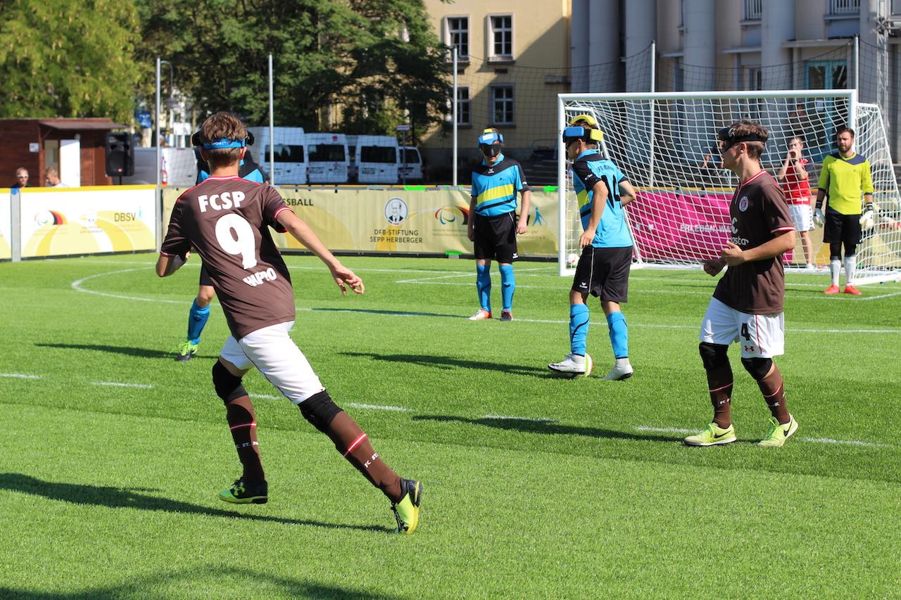 Taime Kuttig (Marburg) dribbelt den Ball in der eigenen Hälfte. Philipp Versen (St. Pauli) nimmt seine Verteidigungsposition ein.
