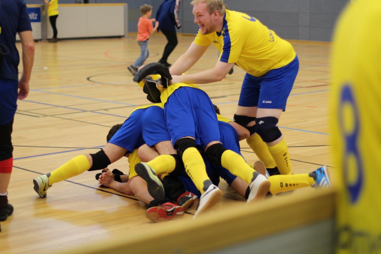 Mikel Preul jubelt neben seinen auf dem Boden liegenden Mannschaftskollegen über den Turniersieg.