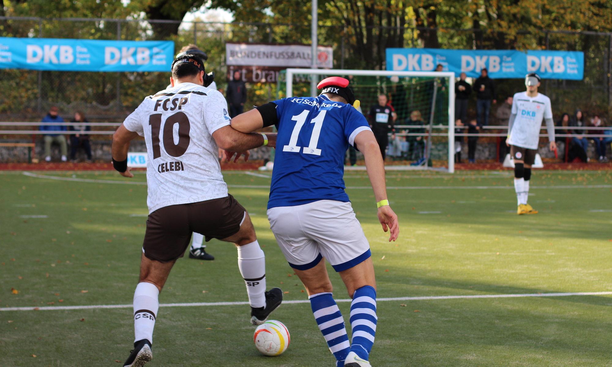 Spielszene im Mittelfeld Serdal Celebi führt den Ball dynamisch in Richtung Mittellinie. Er wird von Hasan Koparan verfolgt. Beide Spieler sind vom Rücken aus zu sehen. Im Hintergrund stehen weitere Spieler auf einem Kunstrasenplatz am Hamburger Borgweg, Foto: Tomke Koop.